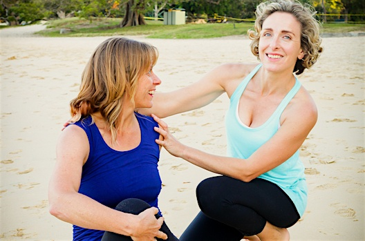Yoga therapist supports a student in a yoga twist on Balmoral beach, Sydney