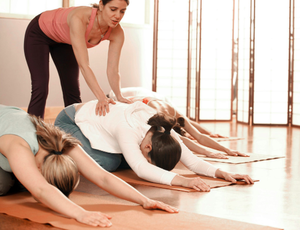 Yoga teacher adjusting in child pose.png