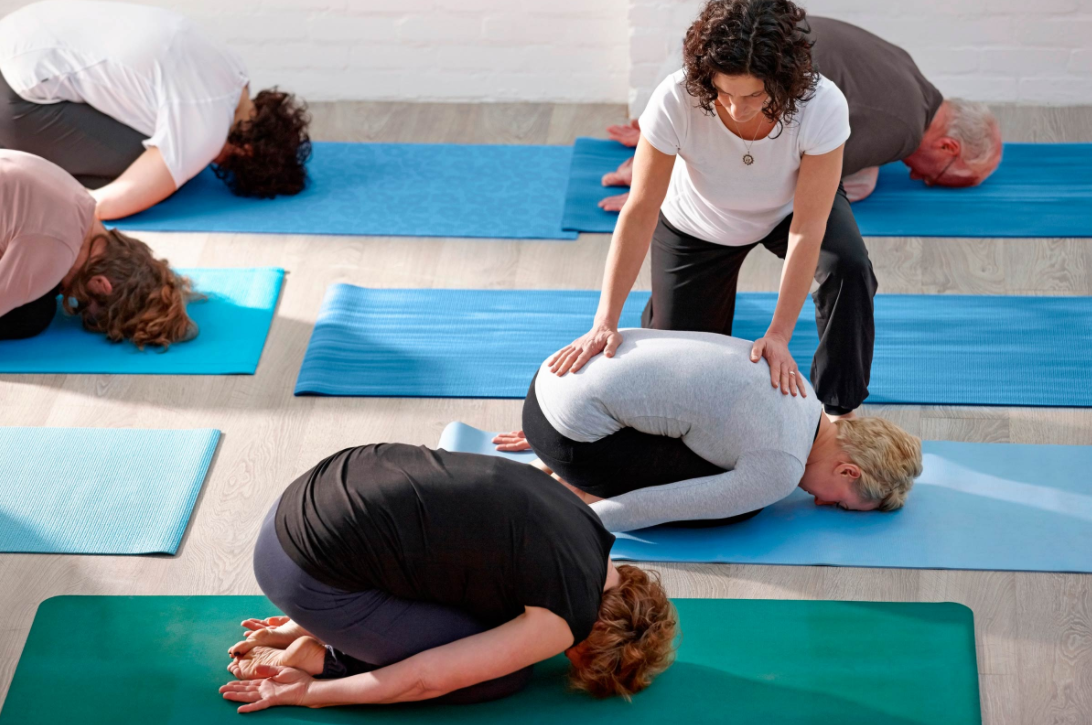 Yoga teacher adjusting in Childs pose.png