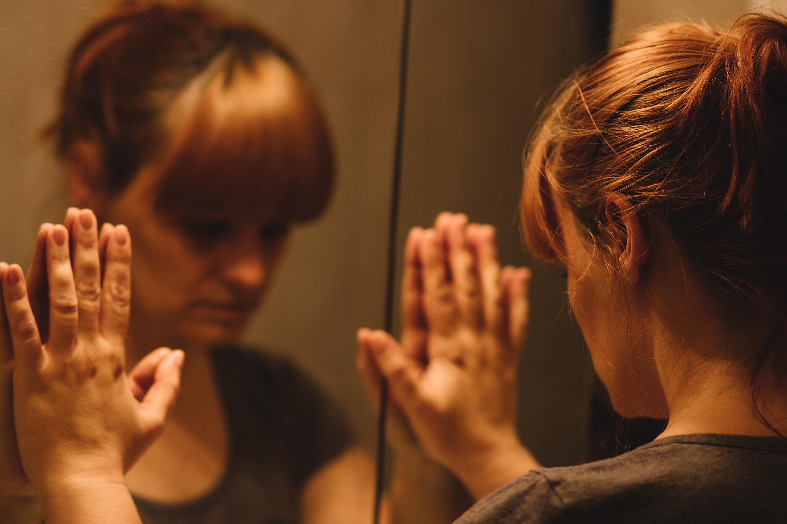Yoga teacher looking in the mirror